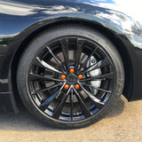 ColorLugs orange colored lug covers on black automobile wheel