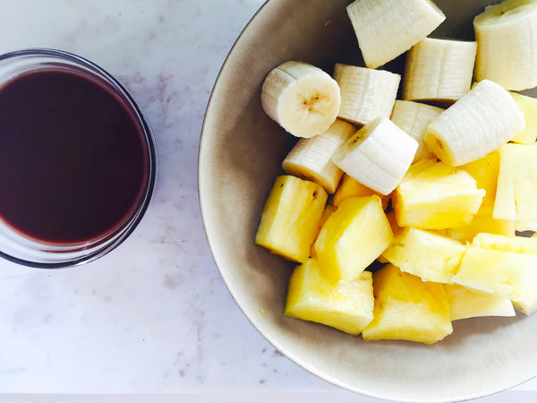 Cut fruit in a bowl with cacao dressing on side