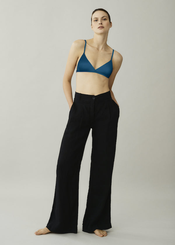 Blue triangle bikini top and black linen wide leg trousers