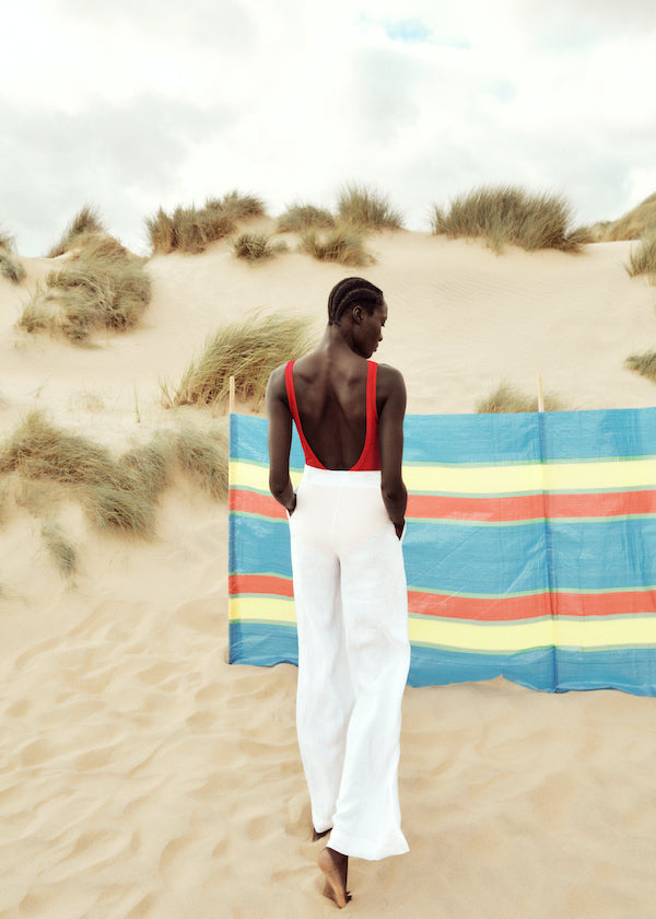 Red v-neck scoop back swimsuit with oversized white linen shirt and white linen wide leg trousers