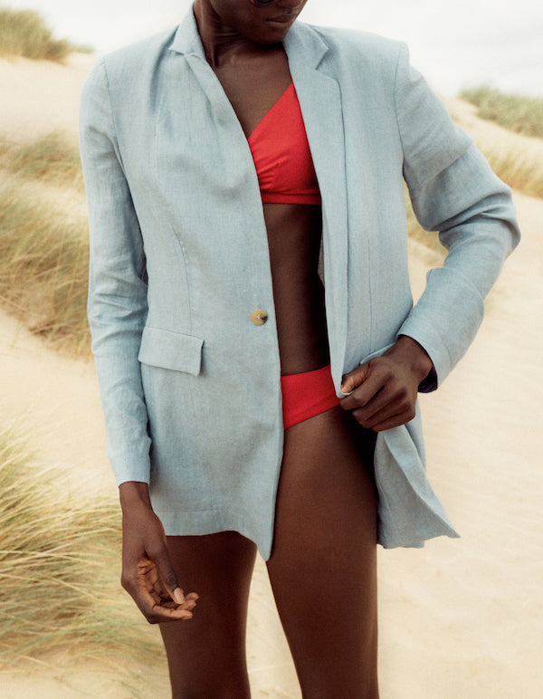 Red triangle bikini top with wide straps, high waist bikini bottom and light blue linen blazer