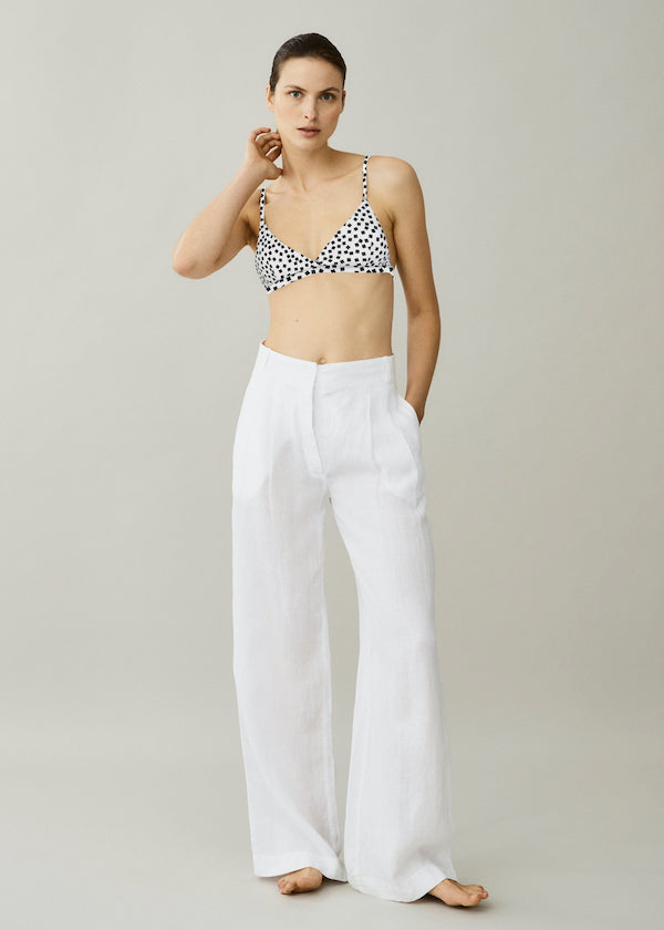 Black and white printed triangle bikini top and white wide leg linen trousers