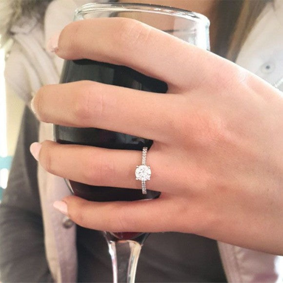 ring finger holding drink engagement announcement