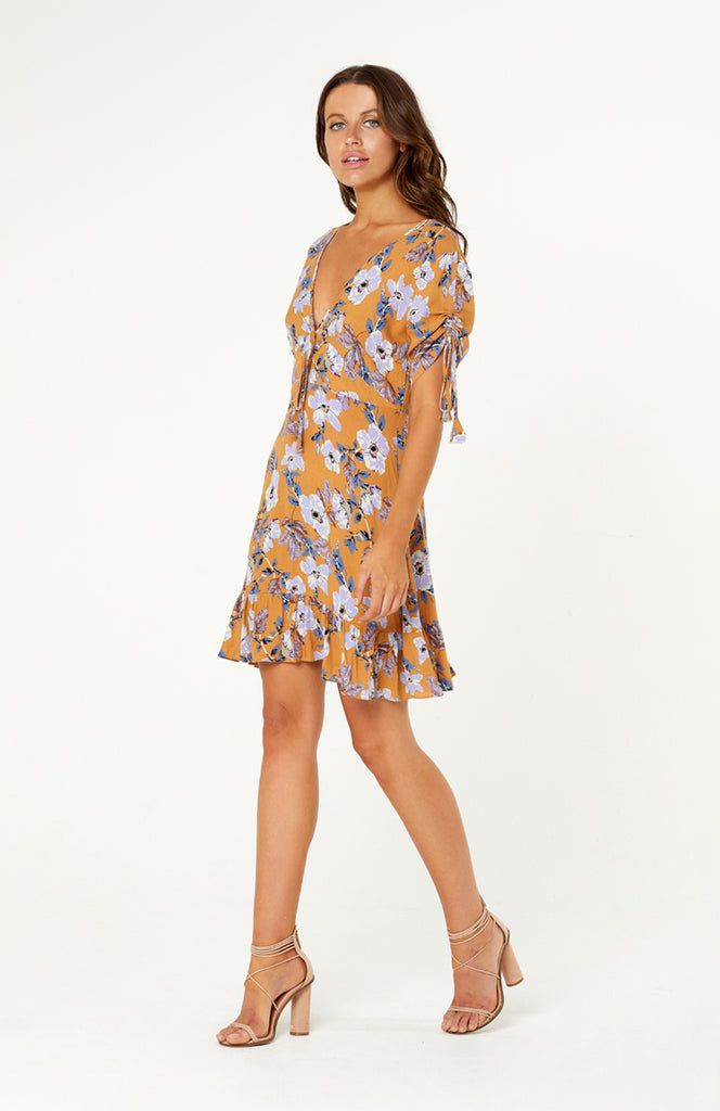 Mexicola Mustard Floral Dress. Empire style dress, v-neckline, feminine bow ties at the front, drawstring sleeves and a ruffled hem, cut-out back detail with button closure. Non-stretch fabric with invisible zip.