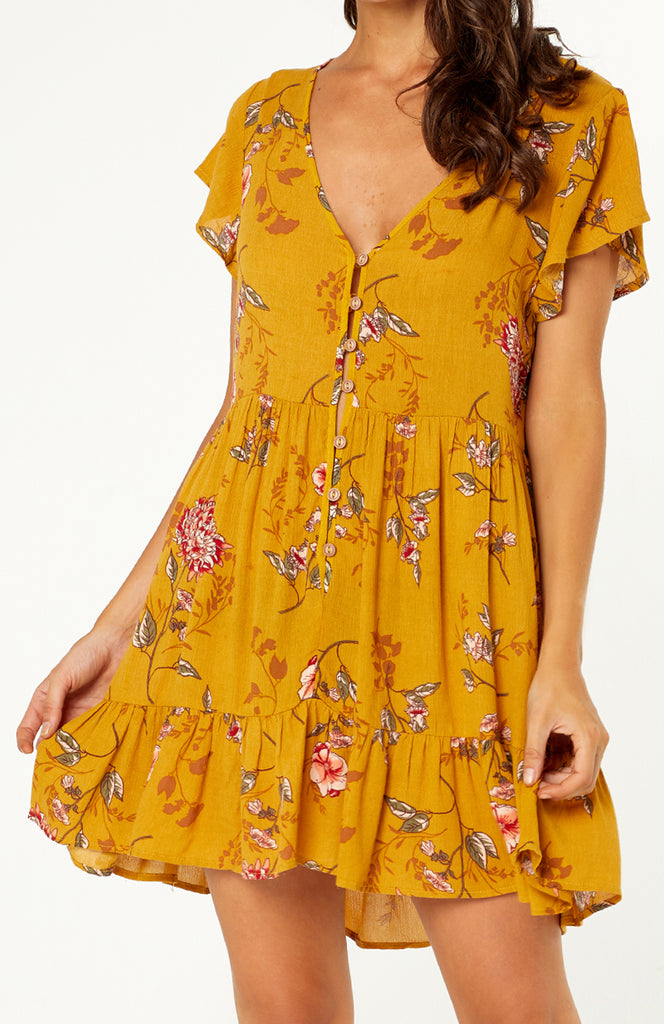 Batu Button Up Floral Dress blends, relaxed fitting mustard dress with v-neck, loose t-shirt sleeves, buttons down the bodice and a full skirt with ruffled hem. Light weight cotton polyester fabric is non-stretch.