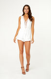 Bahiana Playsuit is a white romper. Features a v-neck with eyelet trim detailing around edges, cutout back, elastic waistline with a bow tie and a soft ruffle hemline. The fabric is non-stretch and has no zips.