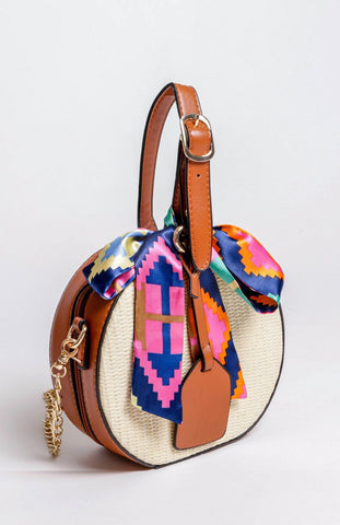 Round straw handbag with tan detail, gold chain and satin printed bow sash