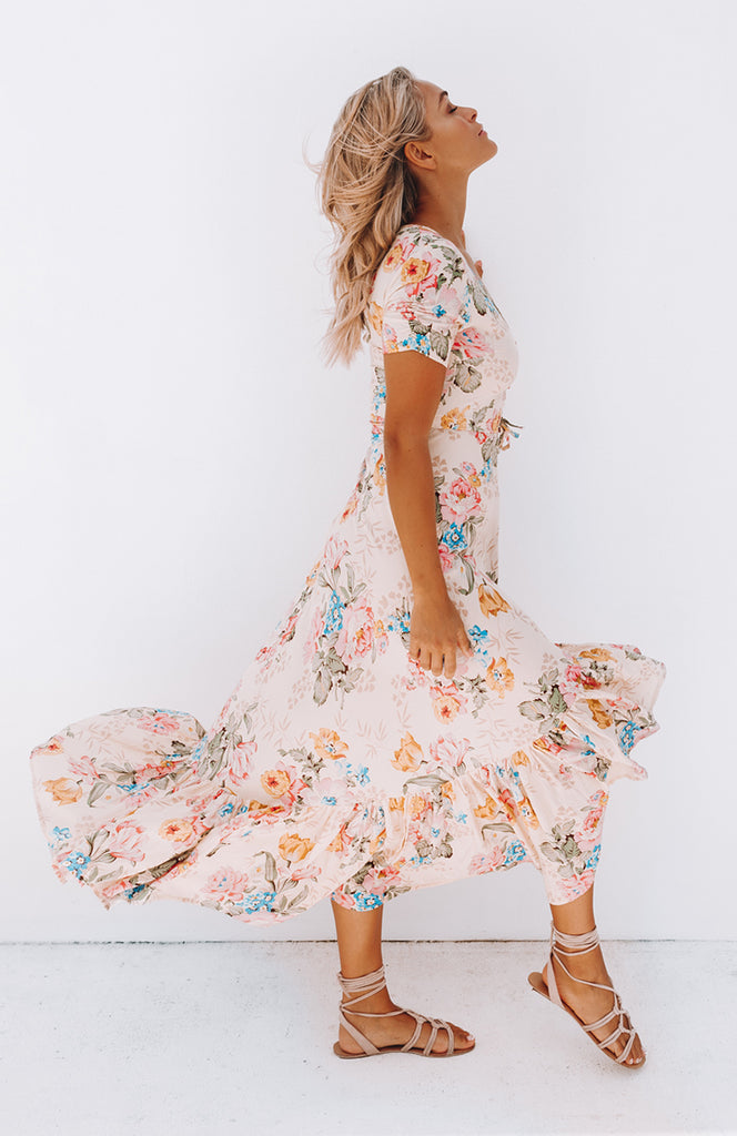 Floral printed high low dress with scoop neckline, buttons down the front, short ruched sleeves, and a spaghetti tie around the waist.