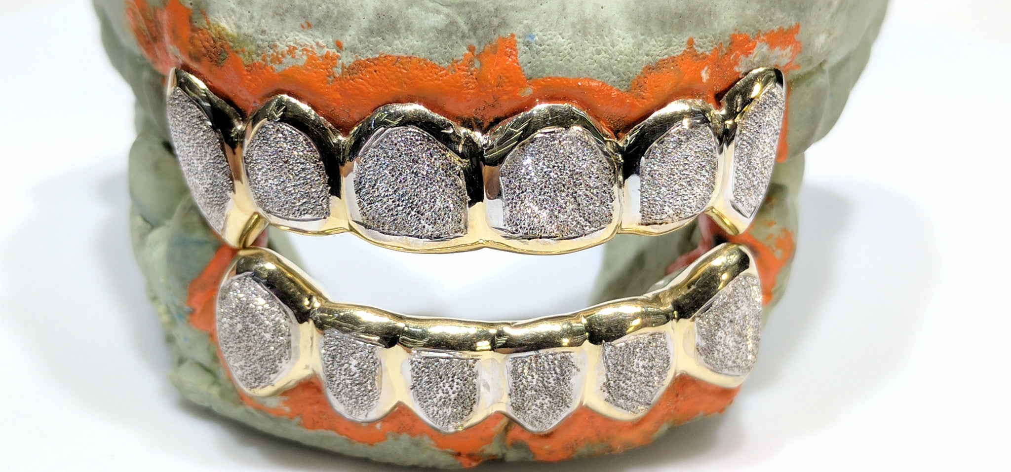 In the center: two bottom and top sets of custom made gold grills in 10 karat yellow gold with two tone rhodium plating high polish and diamond dust laser cut finish made by Popular Jewelry