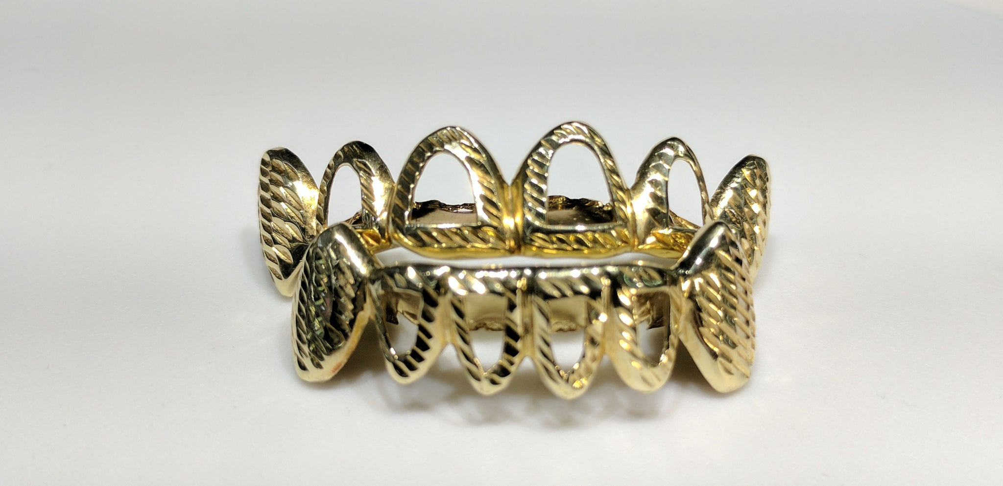 In the center: two sets of bottom and top custom made open face fang grills in 10 karat yellow gold with diamond cut finish made by Popular Jewelry in New York