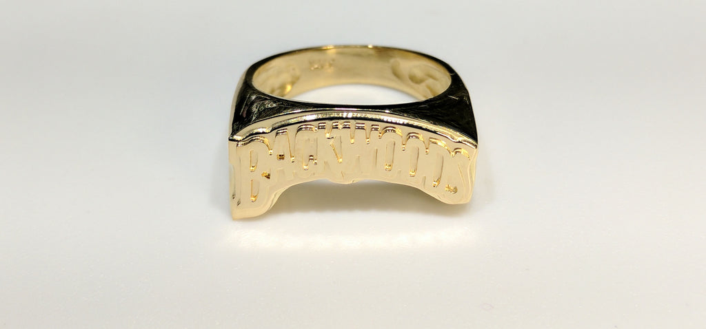 In the center: a custom made name ring stylized Backwoods in 14 karat yellow gold high polish finish double layer made by Popular Jewelry in New York City