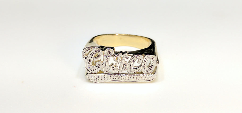 "In the center: a custom made name ring for Francisco stylized ""Ci$co"" in 14 karat yellow gold with two tone high polish white bead work finish made by Popular Jewelry in New York City"
