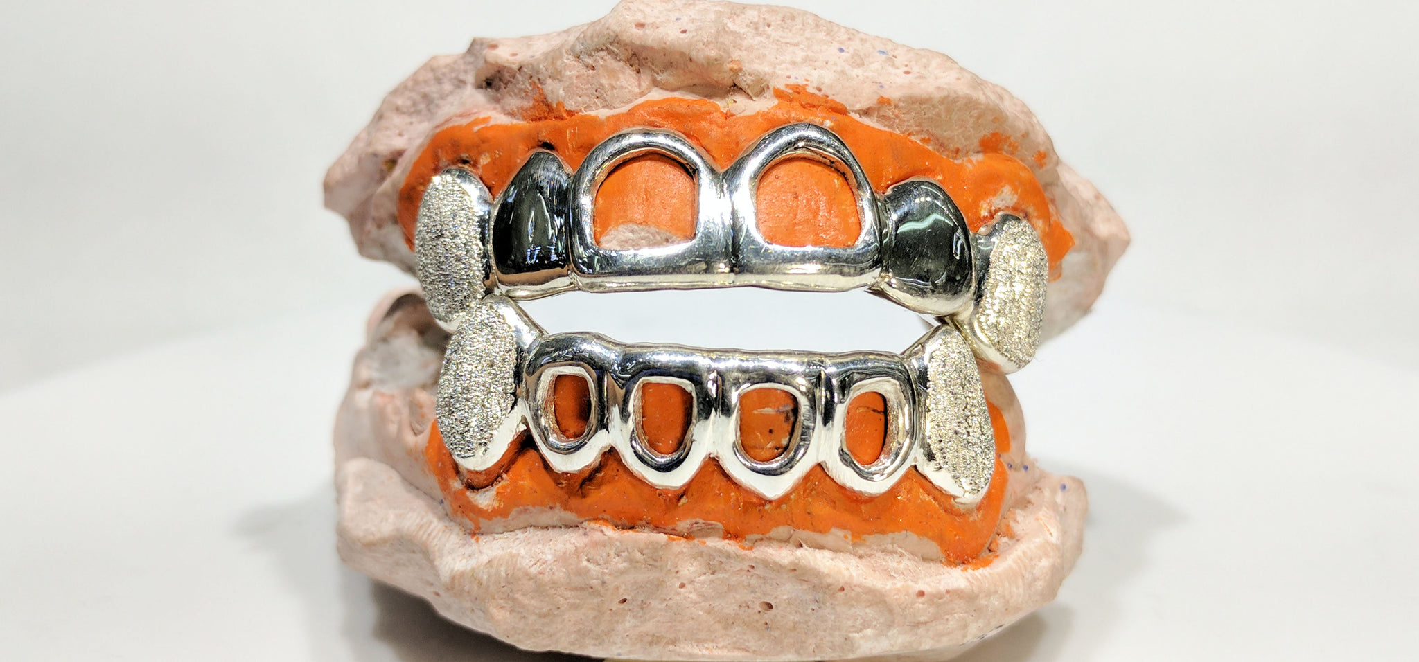 In the center: a custom made sterling silver top and bottom grills with open face and laser cut canines made by Popular Jewelry in New York City for Rujhen