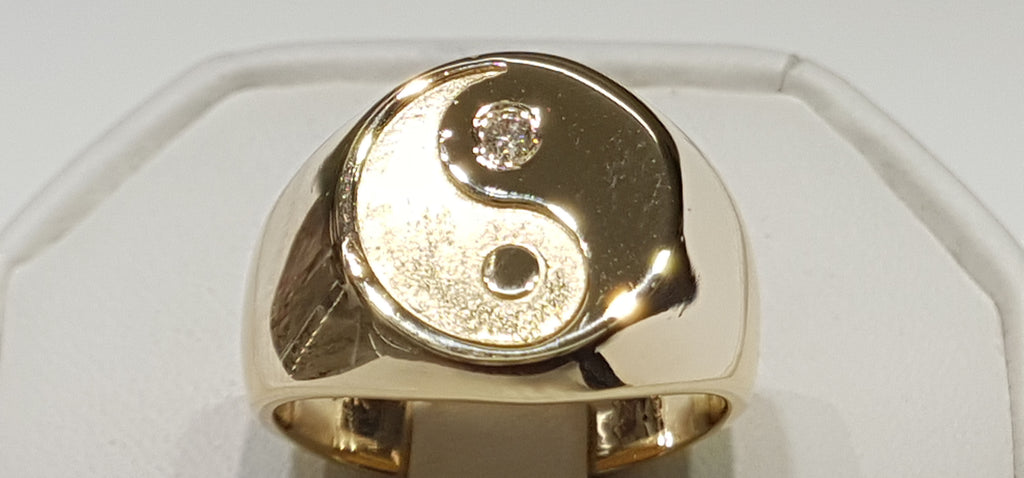 In the center: a custom made signet ring with a Yin Yang design on top in 14 karat yellow gold high polish and diamond made by Popular Jewelry in New York City