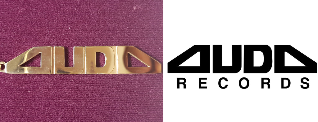 In the center: a custom made 14 karat yellow gold name plate made for Auda Records in high polish finish by Popular Jewelry in New York City