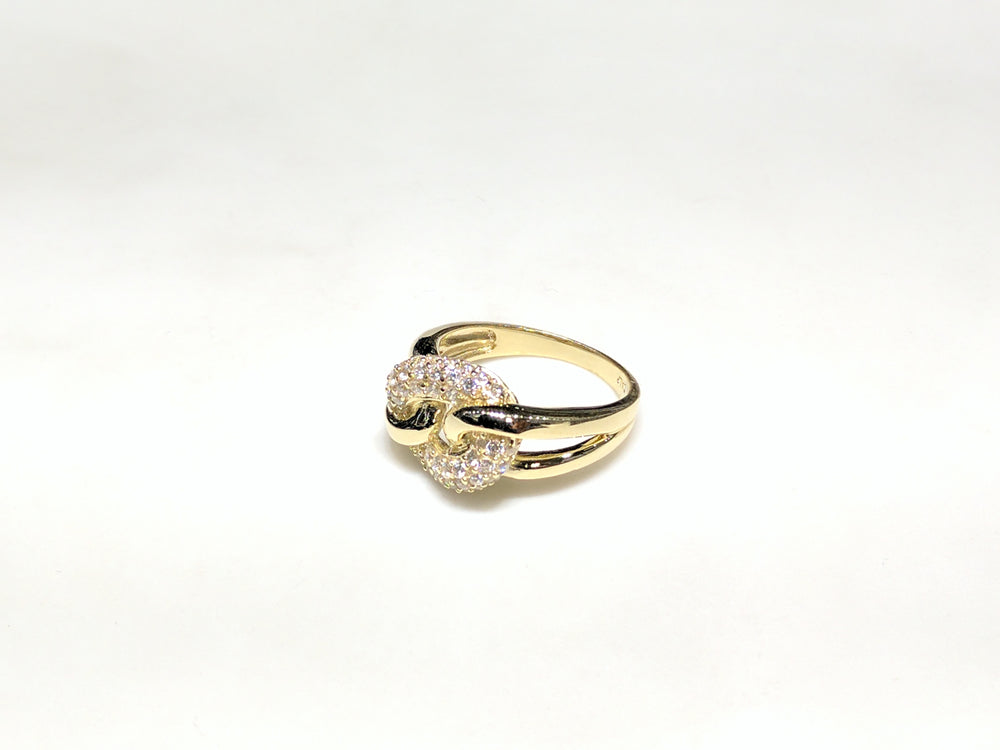 In the center: 10 karat yellow gold lady's puffy round link ring set with cubic zirconia in micro pave setting laying on its side facing the viewer at an angle made by Popular Jewelry