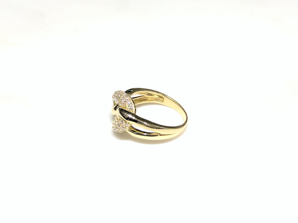 In the center: 10 karat yellow gold lady's puffy round link ring set with cubic zirconia in micro pave setting laying on its side with its left side facing the viewer made by Popular Jewelry