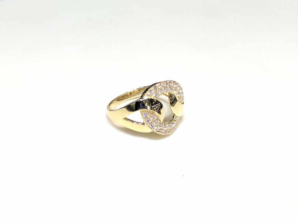 In the center: a 10 karat yellow gold lady's ring in the shape of a flat round link set with cubic zirconia in a micro pave setting laying on its side facing viewer at an angle made by Popular Jewelry in New York City