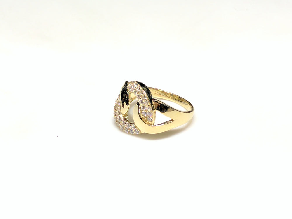 In the center: a 10 karat yellow gold lady's ring in the shape of a flat round link set with cubic zirconia in a micro pave setting laying on its side facing viewer at a different angle made by Popular Jewelry in New York City