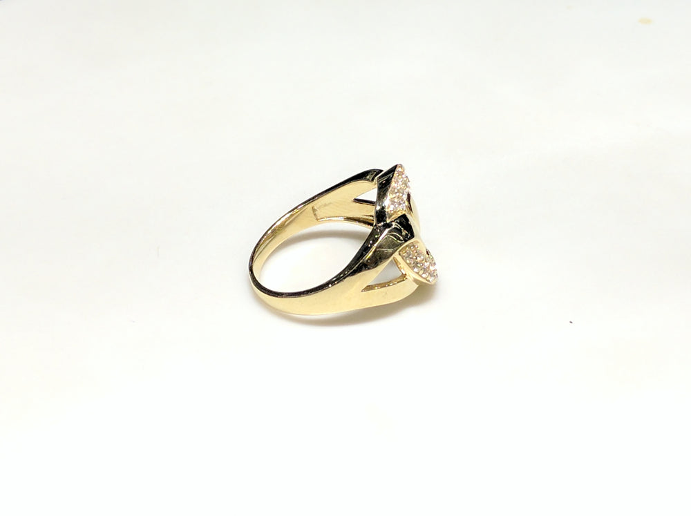 In the center: a 10 karat yellow gold lady's ring in the shape of a flat round link set with cubic zirconia in a micro pave setting laying on its side with its right side facing viewer made by Popular Jewelry in New York City