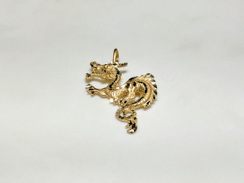 In the center: a 14 karat yellow gold diamond cut eastern asian dragon laying flat frontal view - Popular Jewelry