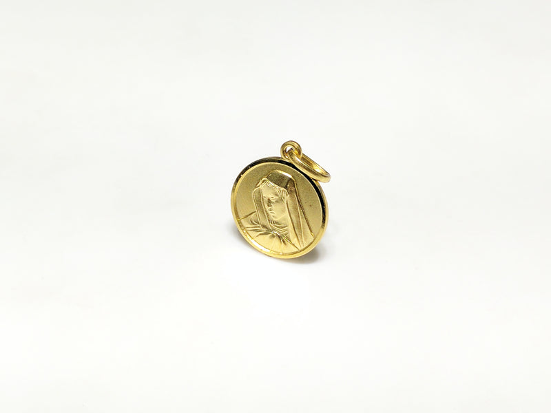 In the center: a portrait of Mary looking downher son Jesus in a 14 karat yellow gold medallion style pendant standing up facing vieweran angle made by Popular Jewelry in New York City