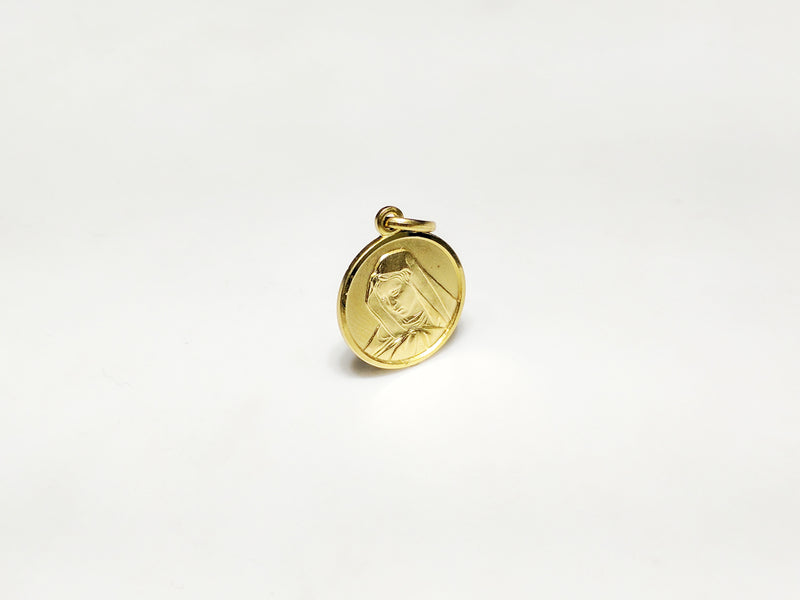 In the center: a portrait of Mary looking downher son Jesus in a 14 karat yellow gold medallion style pendant standing up facing vieweralternate angle made by Popular Jewelry in New York City