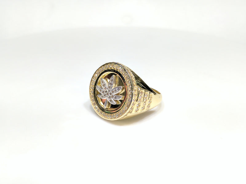 45 angle view of a 10 karat yellow gold signet ring with a white marijuana leaf embedded inside a bezel iced out with cubic zirconia - Popular Jewelry New York