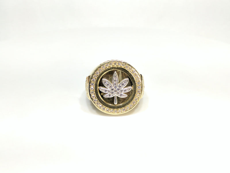 Front view of a 10 karat yellow gold signet ring with a white marijuana leaf embedded inside a bezel iced out with cubic zirconia - Popular Jewelry New York