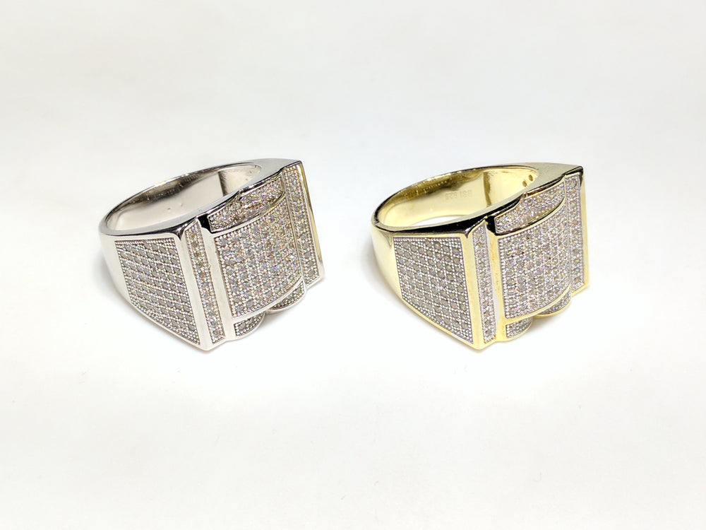 From left to right: white and yellow sterling silver men's rings set with cubic zirconia in a micro pave setting laying side by side at angle view made by Popular Jewelry in New York City