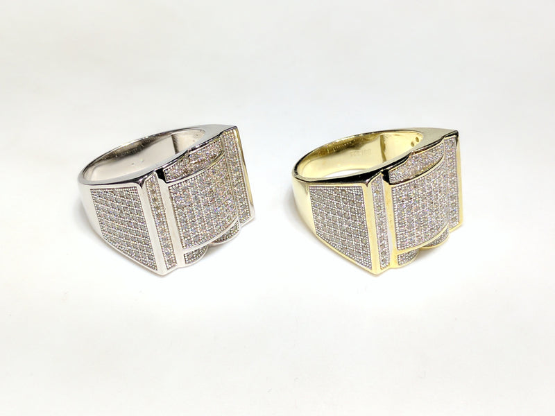 From left to right: white and yellow sterling silver men's rings set with cubic zirconia in a micro pave setting laying side by sideangle view made by Popular Jewelry in New York City