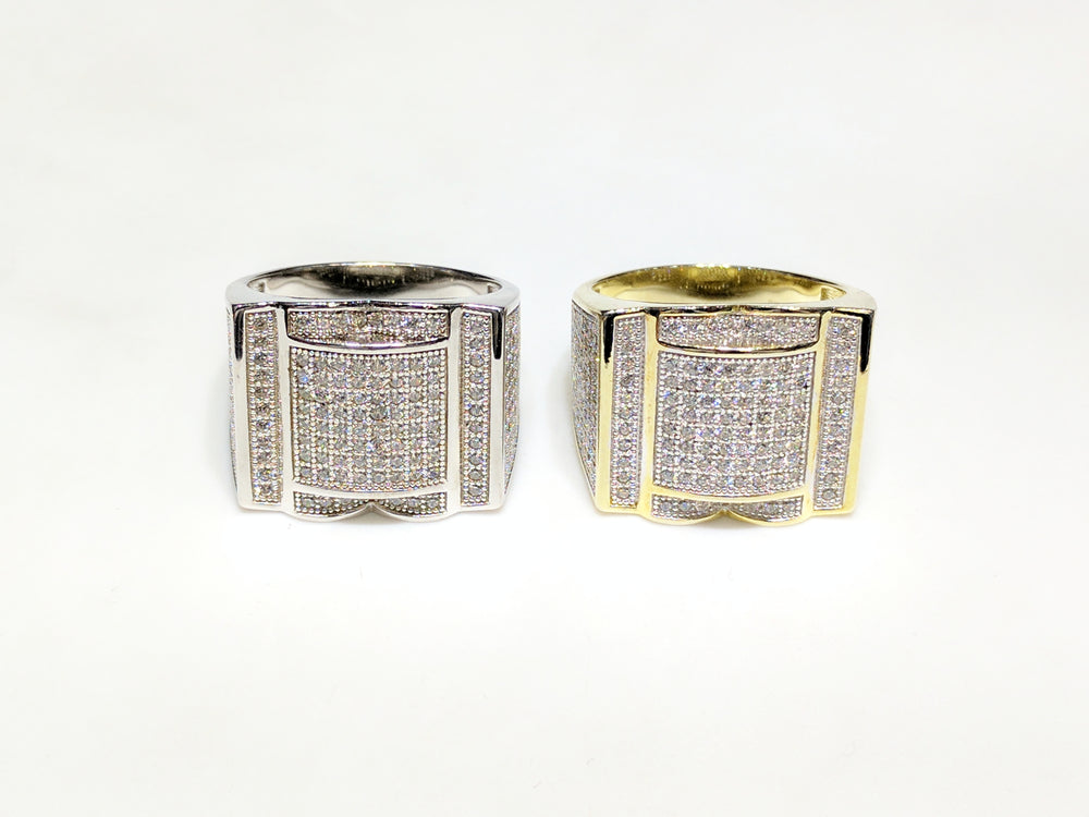 From left to right: white and yellow sterling silver men's rings set with cubic zirconia in a micro pave setting laying side by side facing viewer made by Popular Jewelry in New York City