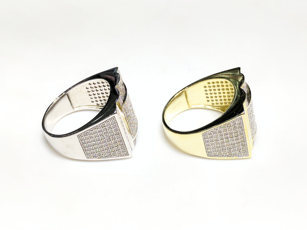 From left to right: white and yellow sterling silver men's rings set with cubic zirconia in a micro pave setting laying side by side in side view made by Popular Jewelry in New York City