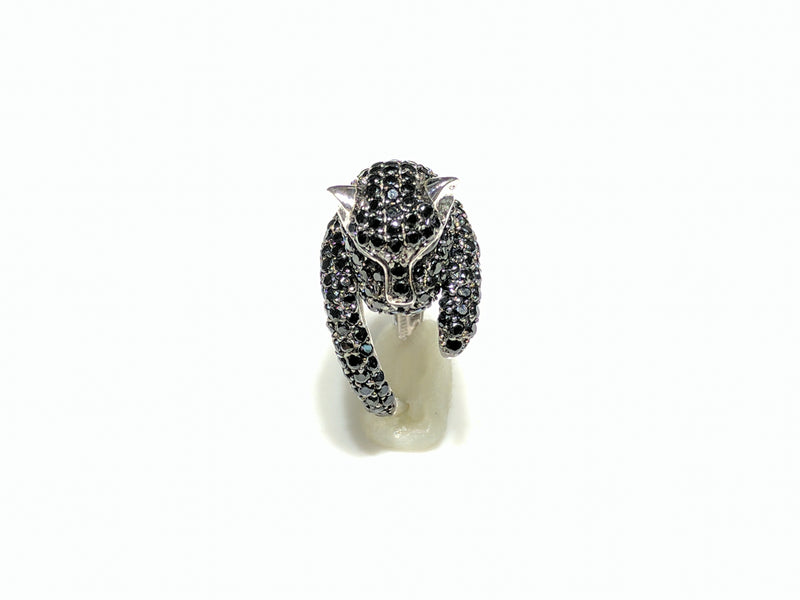 In the center: a sterling silver panther shaped band iced out with black cubic zirconia  in a micro pave setting with its head facing front made by Popular Jewelry in New York City