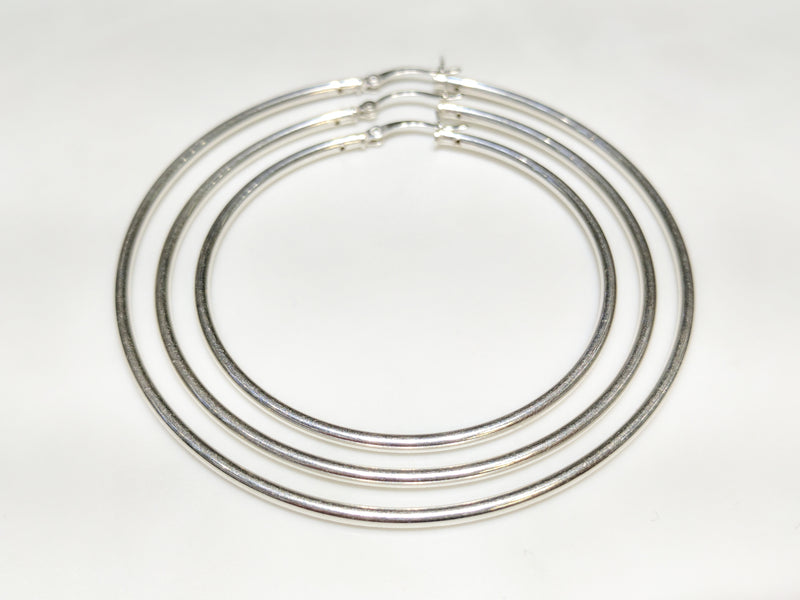 In the center: three sterling silver hoop earrings in plain high polished finish of different diameters arranged within one another from smallest to largest - Popular Jewelry