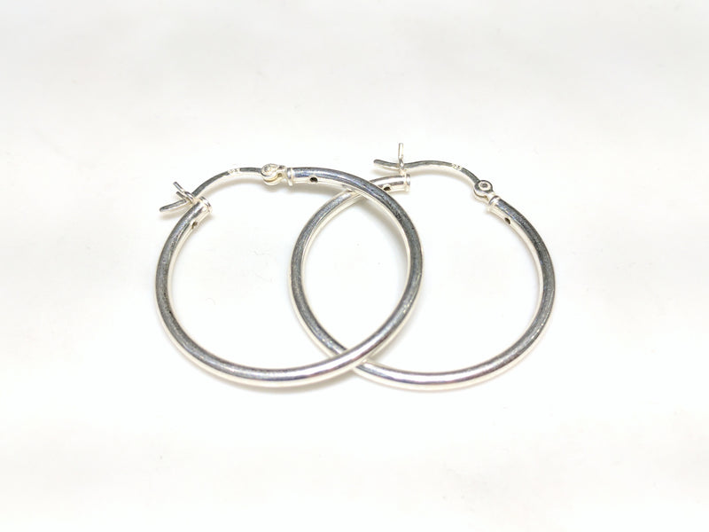 A pair of sterling silver hoop earrings in plain high polished finished stacked and laying flat Popular Jewelry