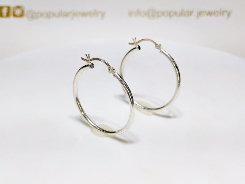A pair of sterling silver hoop earrings in high polished finish standingan angle - Popular Jewelry