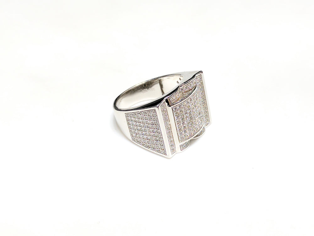 In the center: white sterling silver men's rings set with cubic zirconia in a micro pave setting laying flat at angle view made by Popular Jewelry in New York City