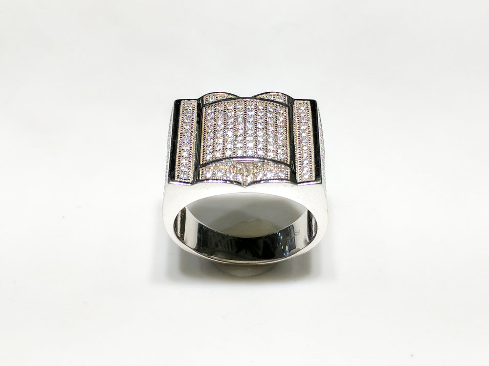 In the center: white sterling silver men's rings set with cubic zirconia in a micro pave setting standing up facing viewer made by Popular Jewelry in New York City