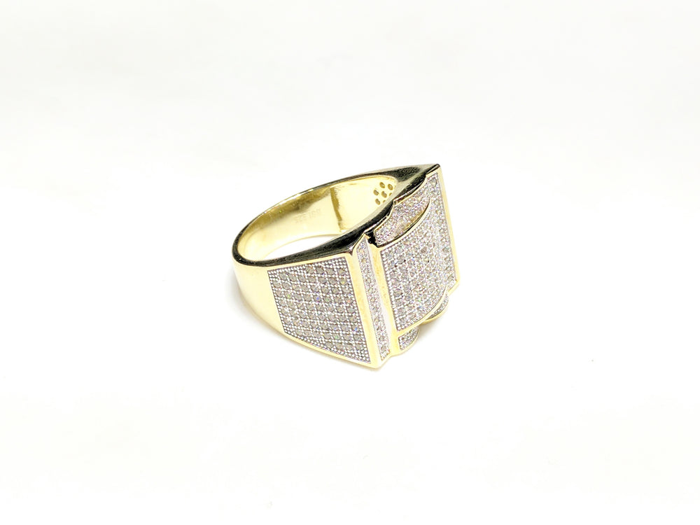 In the center: yellow sterling silver men's rings set with cubic zirconia in a micro pave setting laying flat at angle view made by Popular Jewelry in New York City
