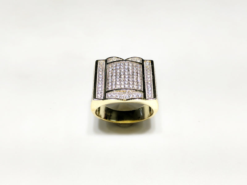 In the center: yellow sterling silver men's rings set with cubic zirconia in a micro pave setting standing up facing viewer made by Popular Jewelry in New York City