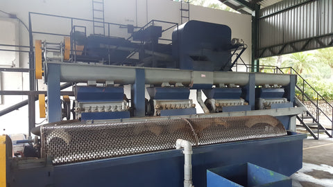 """De-pulping machine that acts like a cylinder grater to separate the fruit from the """"beans"""" in a washed process."""