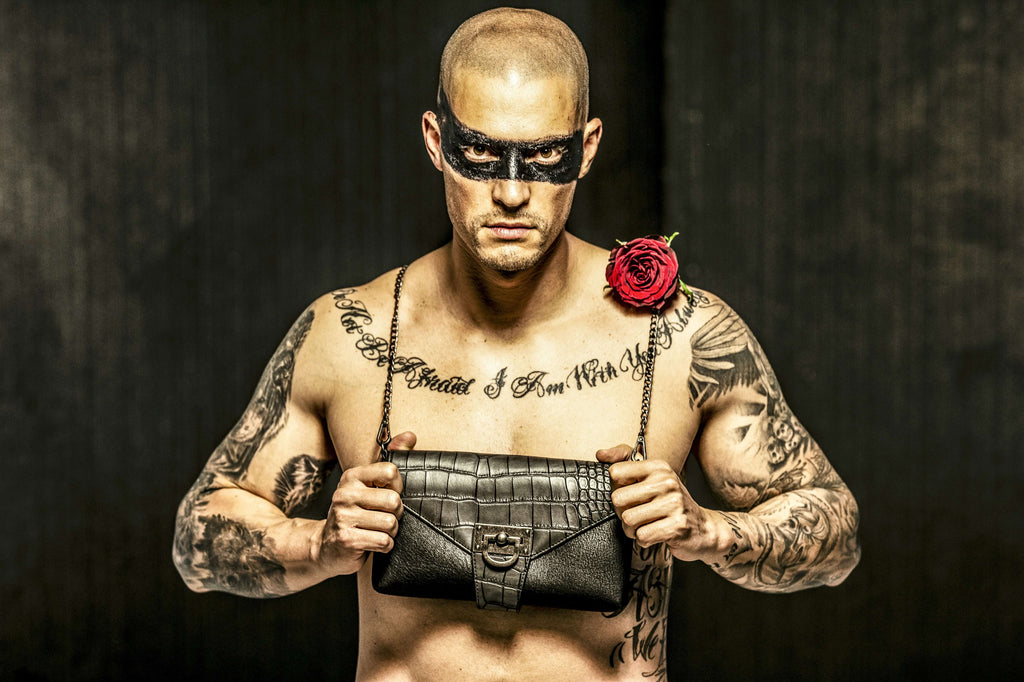 Topless tatooed man (looking at the camera) with a shaved head with a black purse hanging around his neck, with a rose on his shoulder.