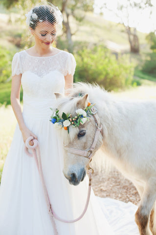 Bride in wedding dress with white pony