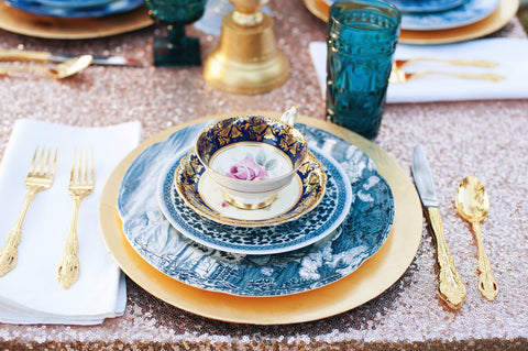 Champagne sequin tablescape with gold and blue table setting.