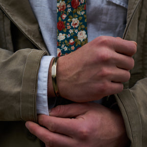Image of the brass cuff bracelet and Posie floral tie by Dear Martian, Brooklyn.