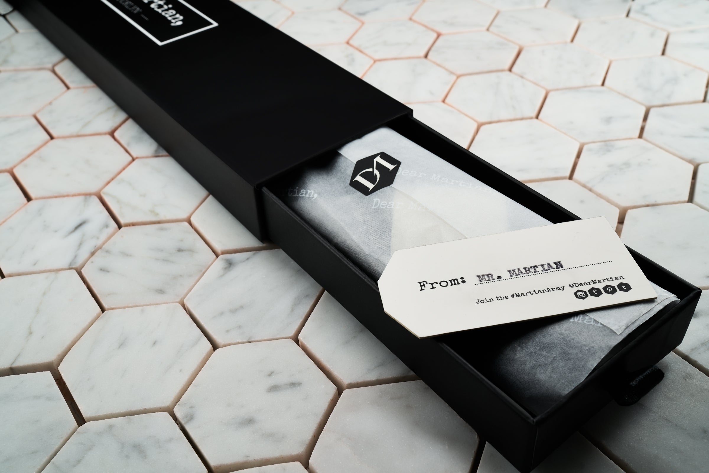 An image of Dear Martian, pull-out style box which contains a black and white checkered tie wrapped in DM gift wrapping. The wrapping is sealed with a DM hexagonal logo and in addition contains a personalized hang tag label with the Martian's name.