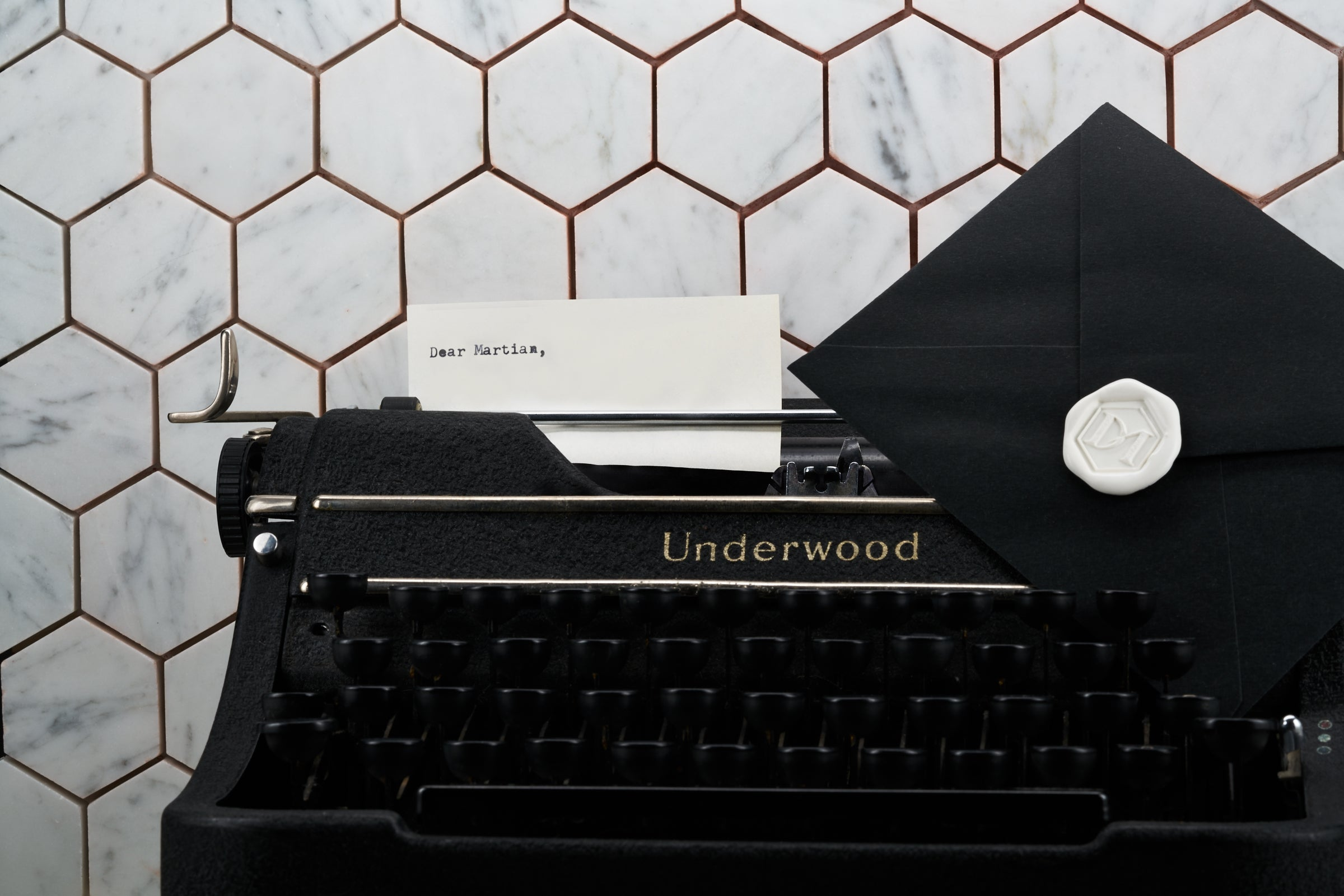 "An image of the special gift add-on to a customer cart. The image depicts a vintage underwood typwriter with a letter containing the text ""Dear Martian,"". In a addition the photo shows a black matte envelope with a hexagon DM wax seale"