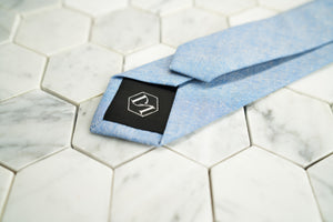 A detailed picture of the back of Dear Martian's aqua blue chambray necktie. The tipping of the tie contains the hexagonal DM logo.