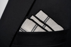 Dear Martian's Lexington Ave white linen argyle pocket square with black border is shown with a three-point fold.